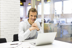 Businessman in the office on the phone with headset, Skype Royalty Free Stock Photos