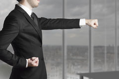 Businessman in office punch karate pose Royalty Free Stock Photography