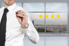 Businessman in office pushing button four golden rating stars Stock Photos