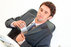 Businessman in office putting money in pocket Stock Photography