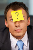 Businessman in office with question mark written on adhesive not Stock Image