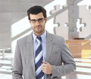 Businessman at office reception. Confident businessman at office reception, puzzle decoration in background Stock Photo