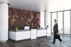 Businessman at office reception. Side view of young businessman looking at modern reception desk with empty poster in interior with city view and daylight Stock Photo