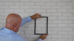 Businessman in office room find photo frame position decorating interior wall.  stock video footage