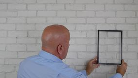 Businessman In Office Room Try to Find a Position on the Wall for a Frame.  stock footage