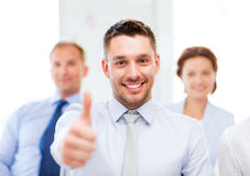 Businessman in office showign thumbs up Stock Images