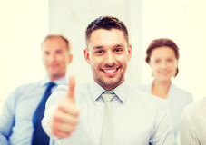 Businessman in office showign thumbs up Royalty Free Stock Photos