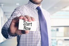 Businessman in office showing card with text: Start now. Businessman in office showing card with text stock image