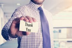 Businessman in office showing card with text: Thank You. Businessman in office showing card with text Royalty Free Stock Photo
