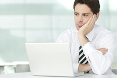 A businessman in an office sitting at laptop, looking bored Royalty Free Stock Image