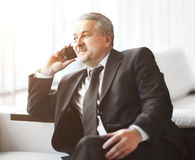 Businessman in office sitting on sofa talking on phone Stock Image