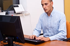 Businessman in office. Businessman sitting and using keyboard in office Royalty Free Stock Image