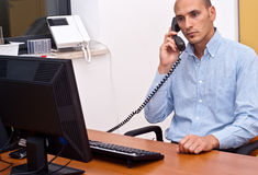 Businessman in office. Businessman sitting and using phone in office Royalty Free Stock Photo