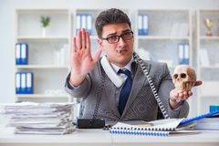 The businessman in the office smoking holding human skull Stock Image