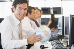 Businessman in office space with a desk globe Royalty Free Stock Photography