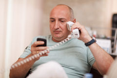 Businessman in the office speaking on two phones Stock Image