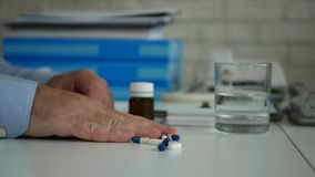 Businessman in office suffering a big headache take medical pills from the table.  stock video