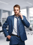 Businessman in office talking on cell phone Stock Images