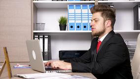 Businessman in office typing on the laptop. In his office stock video