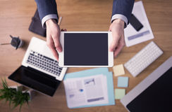Businessman at office using a digital tablet. Businessman working at office desk and using a touch screen digital tablet, laptop and stationery on background royalty free stock image