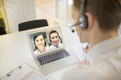 Businessman in the office on videoconference with headset, Skype stock photos