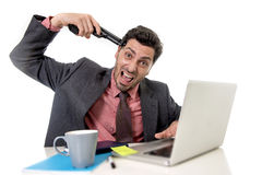 Businessman at office working on computer laptop pointing gun to tempo in suicide gesture Stock Photography