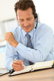 Businessman at office working with headset Stock Images