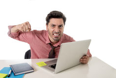 Businessman at office working stressed on computer laptop overworked throwing punch in work stress. Young attractive businessman sitting at office desk working Royalty Free Stock Photo