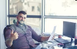 Businessman in office, at workplace with contract in hands. Happy and satisfied businessman. Good news and good work stock images