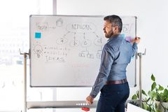 Businessman in the office writing notes on whiteboard. Handsome young businessman with gray hair in the office writing notes on whiteboard, setting goals Royalty Free Stock Image