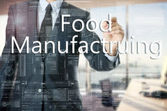 The businessman in the office is writing on the transparent board: Food Manufacturing