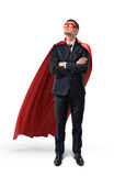 A businessman in an official suit and red cape with hands crossed and looking up. Royalty Free Stock Image