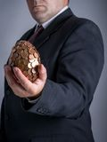 Businessman with one eurocent egg. Businessman wearing black suit holding one eurocent egg in his hand Royalty Free Stock Image