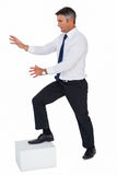 Businessman with one foot on a cube and arms out Royalty Free Stock Image
