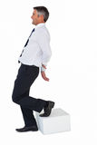 Businessman with one foot on cube and hands behind his back Stock Photography