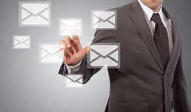 Businessman open email. Business man open email touching icon on screen, grey background Royalty Free Stock Image