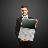 Businessman with open laptop in his hands. Smiles at camera Stock Photography