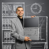 Businessman with open laptop in his hands. Smiles at camera Stock Photos