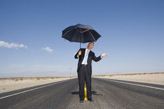 Businessman on open road in desert with umbrella, feeling for rain, low angle view Royalty Free Stock Images