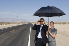 Businessman on open road in desert using binoculars by businesswoman with umbrella Stock Image