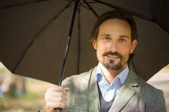 Businessman with opened umbrella Stock Photos