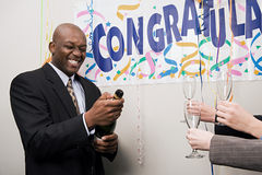Businessman opening a bottle of champagne Stock Photography