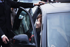 Businessman opening car door for businesswoman during the day in Beijing Stock Photo