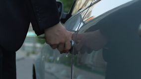 Businessman opening car with key and getting into automobile, private property. Stock footage stock video footage