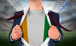 Businessman opening shirt to reveal ivory coast flag Stock Photo