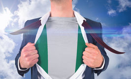 Businessman opening shirt to reveal nigeria flag Royalty Free Stock Photography