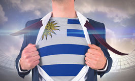 Businessman opening shirt to reveal uruguay flag Stock Photo