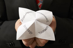 Businessman and origami. Business man holding origami fortune teller with teamwork,leadership,innovation and strategy written on it royalty free stock photography