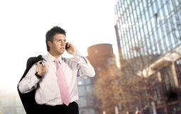 Businessman outdoor. Young businessman walks and talks on a mobile phone, outdoor portrait Royalty Free Stock Images