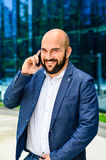 Businessman outdoor. Handsome bearded smiling    businessman talking at the phone Stock Photography